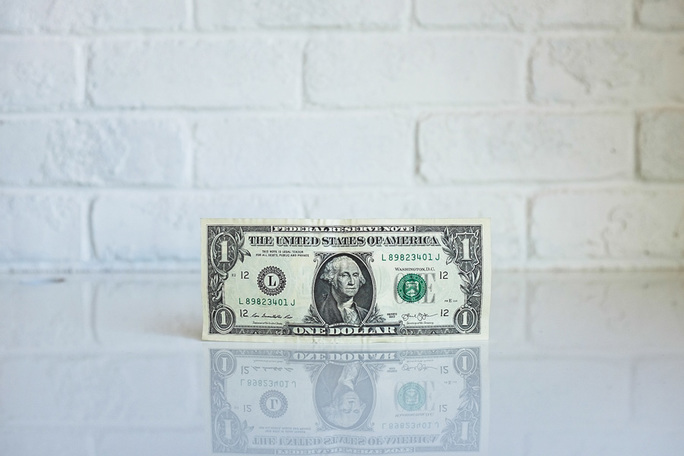 crisp dollar bill in front of white brick wall